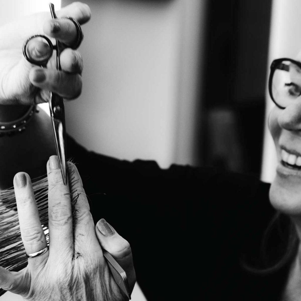 Kapster Maria Rood die haar knipt in haar kapperszaak, in zwart wit